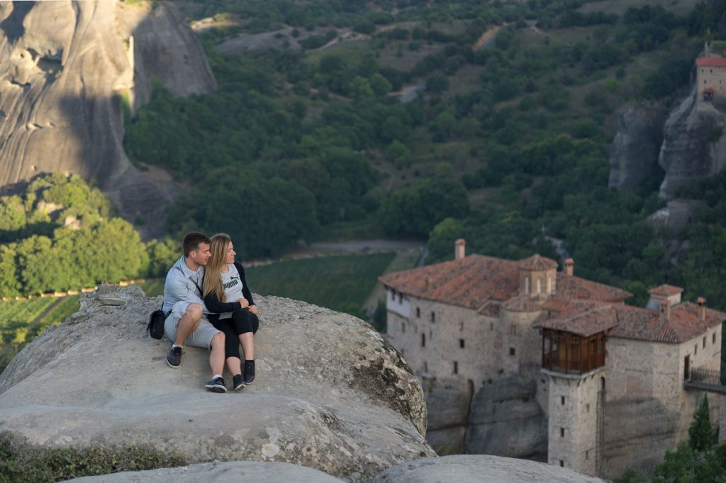 A couple ssitting on the rocks of Meteora during the morning light
