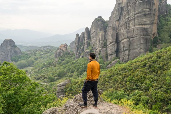 Photo shoot in Meteora backdrop while the man looking the stunning view