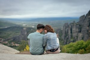 A lovely couple siting on the rocks of Meteora