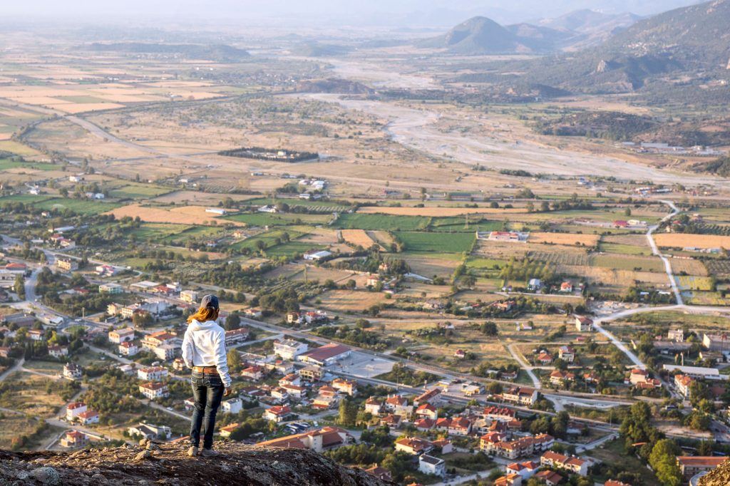 Meteora Photo shooting while the girl standing and looking at the view of the valley of Thessaly