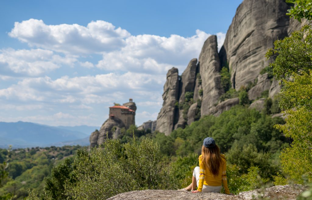 The blogger sitting on the rock of Meteora watching the Monastery