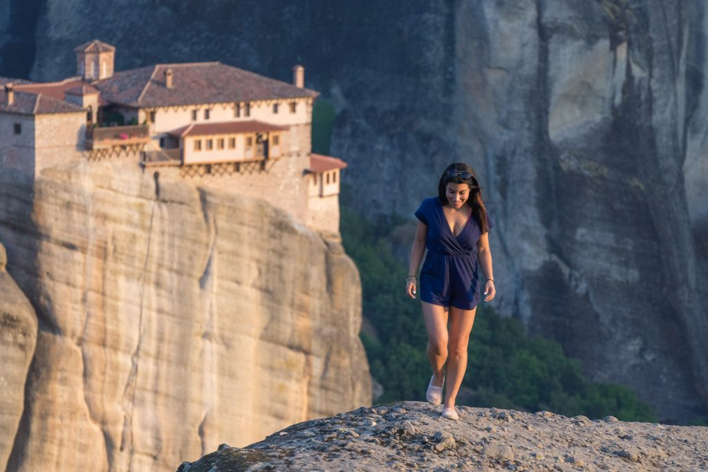 A girl walking on the rocks of Meteora during the golden light