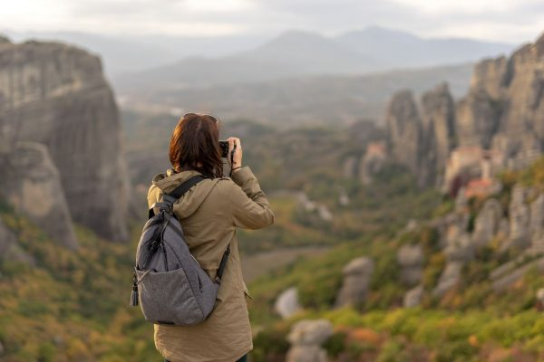 A girl photograph the beautifull Meteora backdrop in fall colors