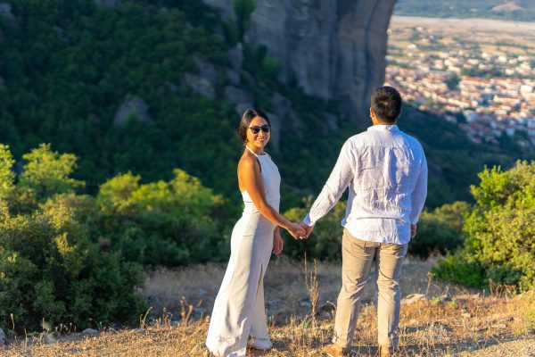 Beautiful couple posing against the backdrop of Meteora rocks and the city of Kalambaka