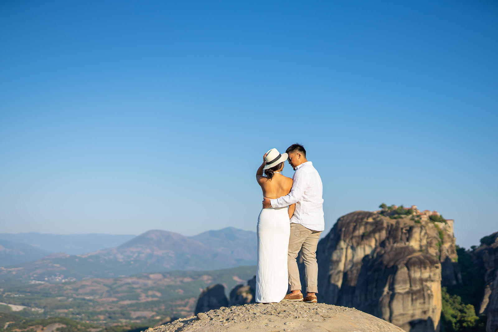 A cople on a rock of Meteora during the photo shooting