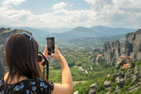 girl from Singapure photograph the Meteora landscape using her mobile phone