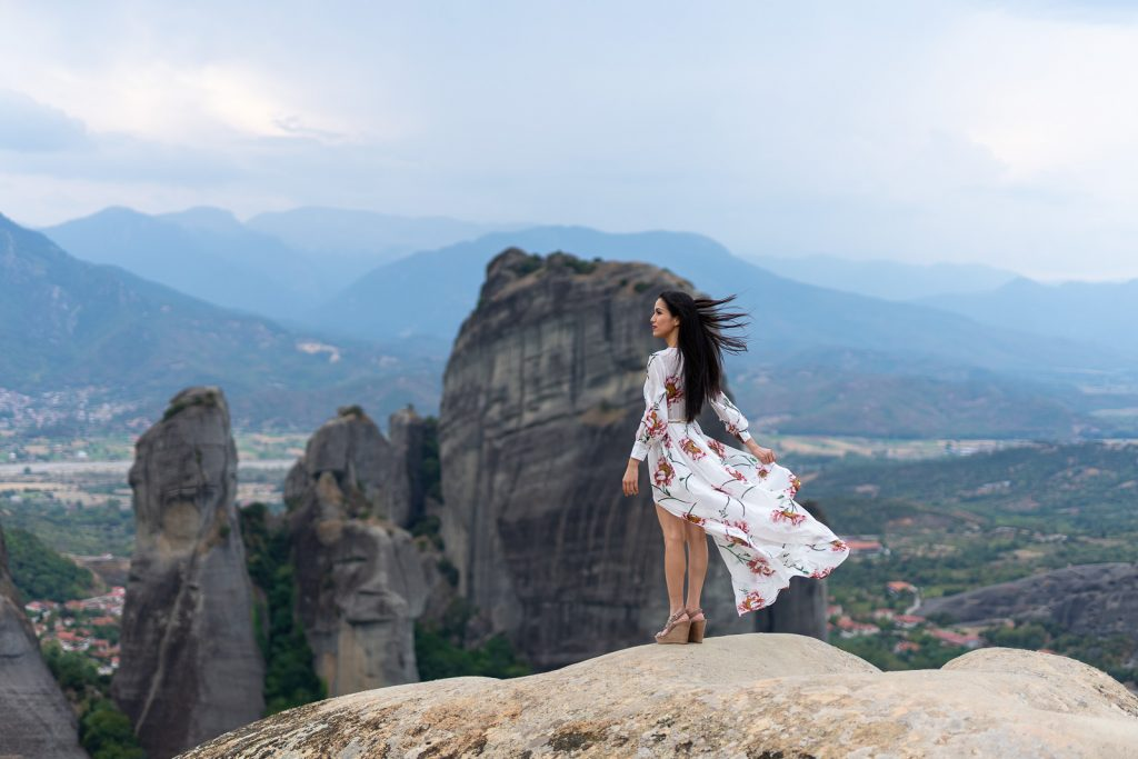 The girl with the flowering white dress possing on the rocks of Meteora