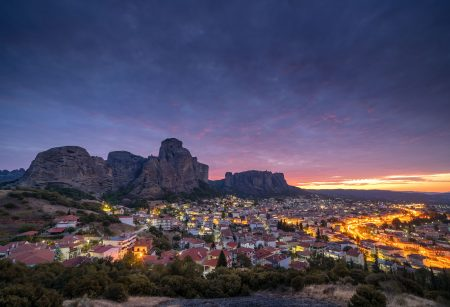Sunrise over Meteora and the city lights of Kalampaka.
